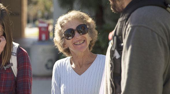 Photograph of Dr. Eve Kornfeld, smiling and talking with a student at an outdoor event.